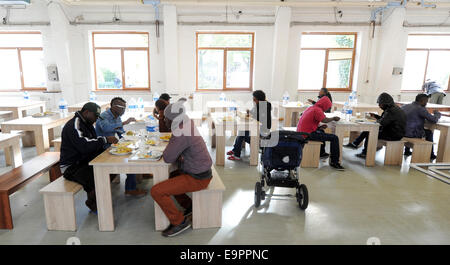 Munich, Germany. 31st Oct, 2014. Refugees sit in the cafeteria at the reception center for asylum seekers on the - Stock Photo