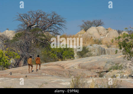 San bushman trackers walking on the ancient granite outcrop of Kubu Island (Lekhubu), Makgadikgadi Pan, Botswana - Stock Photo