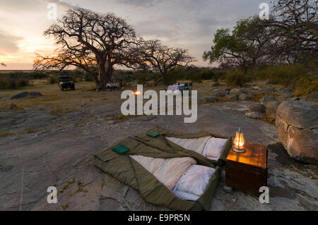 Camping beds of a luxury private safari camp on the granite mass of Kubu Island (Lekhubu) at sunset, Magkadigkadi - Stock Photo