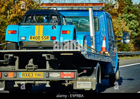 A pale blue Caterham sports car strapped onto a recovery vehicle, being driven in England, UK. - Stock Photo