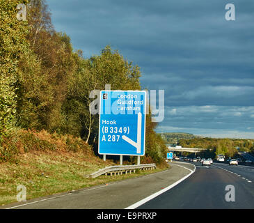 Hook exit sign in the warm early evening sunshine, on the M4 motorway in Hampshire, England, UK. Straight ahead - Stock Photo