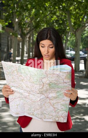 angry brunette woman watching a map at street in Madrid city Spain - Stock Photo