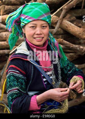 Black Hmong woman dressed in traditional attire and working with thread at Ta Van village, near Sapa, North Vietnam. - Stock Photo