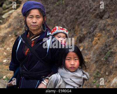 Hmong woman wearing traditional attire, with baby and young daughter on the trail to Ta Van village near Sapa, Lao - Stock Photo
