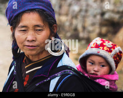 Hmong woman wearing traditional attire and jewelry and carrying an unidentified infant child in Sapa Town, North - Stock Photo