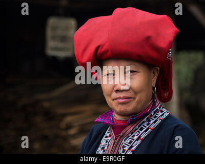Woman from Red Dao minority group wearing traditional attire and headdress near Sapa Town, Lao Cai Province, Vietnam. - Stock Photo
