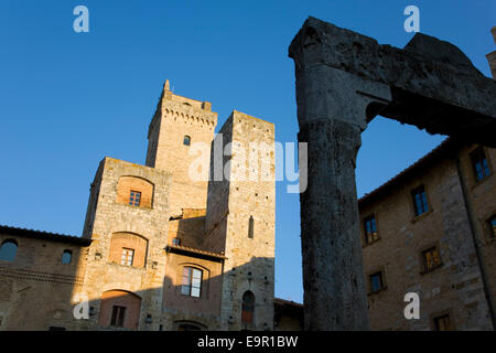 San Gimignano, Tuscany, Italy. Sunlit medieval towers overlooking Piazza della Cisterna, 13th century well in foreground. - Stock Photo