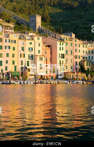 Portovenere, Liguria, Italy. View across the harbour to colourful houses, sunrise. - Stock Photo