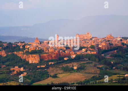 Orvieto, Umbria, Italy. View to the city skyline across agricultural landscape, sunset. - Stock Photo