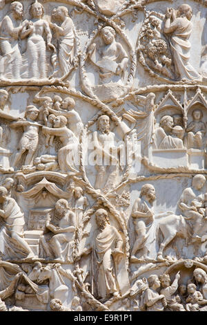Orvieto, Umbria, Italy. Intricately carved bas-relief depicting scenes from the New Testament on façade of the cathedral. - Stock Photo