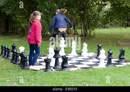 Children playing on a giant garden chess set - Stock Photo
