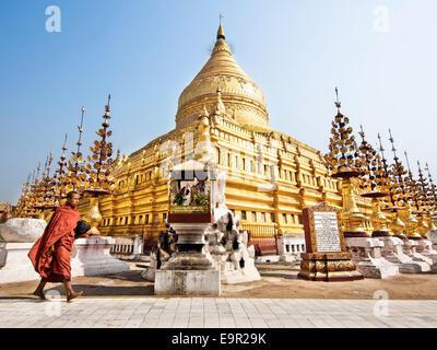 A Buddhist monk walking around sacred Shwezigon Paya, one of Myanmar's most revered pagodas, in Bagan, Myanmar (Burma). - Stock Photo