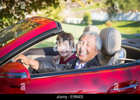 Attractive Happy Chinese Couple Enjoying An Afternoon Drive in Their Convertible. - Stock Photo