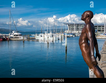 Max Patte's statue Solace of the Wind, bronze figure leaning over the dockside near the marina in Wellington Harbour, - Stock Photo