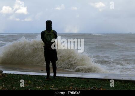Chicago, Illinois, USA. 31st October, 2014.  A photographer takes shots of raging Lake Michigan during today's gale. - Stock Photo