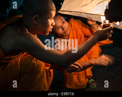 Two orange-robed Buddhist monks lighting up a rice paper hot air balloon at the Loy Krathong festival in Chiang - Stock Photo