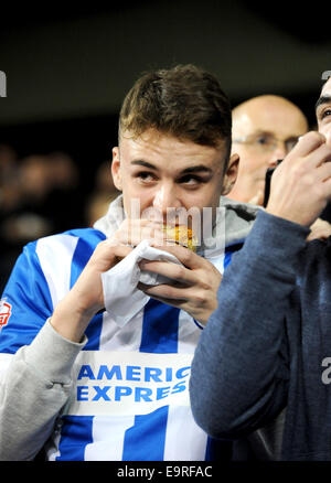 Brighton and Hove Albion football fan eating a pie on the terraces of ground - Stock Photo