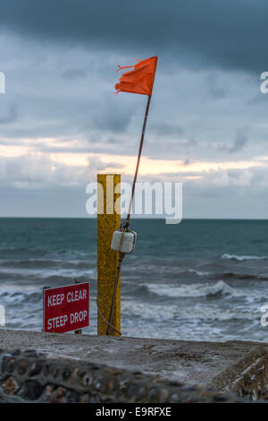 Keep Clear Steep Drop warning sign on the beach next to an orange flag against a stormy backdrop - Stock Photo