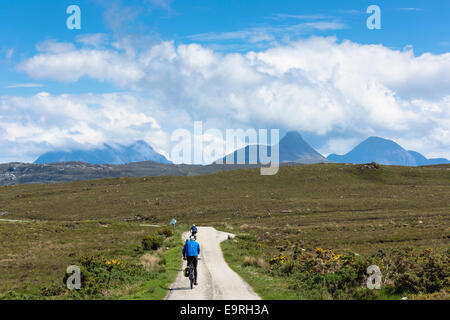 Tourists cycling by Stac Pollaidh - Stack Polly - (centre) in glacier mountain range in the North West Highlands - Stock Photo