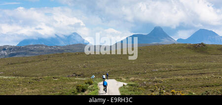 Tourists cycling by Stac Pollaidh - Stack Polly - in glacier mountain range in the North West Highlands Geopark - Stock Photo