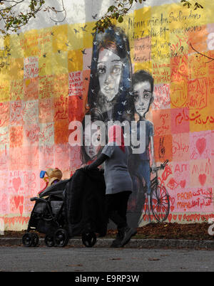 Munich, Germany. 31st Oct, 2014. A Syrian woman pushes her pram in front of a mural at the reception center for - Stock Photo