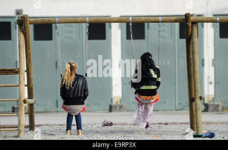 Munich, Germany. 31st Oct, 2014. Two refugee sit in swings at the reception center for asylum seekers on the Bavaria - Stock Photo