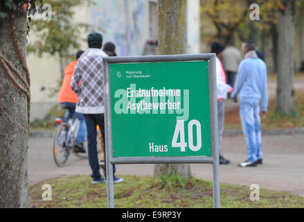 Munich, Germany. 31st Oct, 2014. Refugees walk behind a sign at the reception center for asylum seekers on the Bavaria - Stock Photo