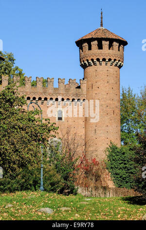 The tower of the medieval castle in the Valentino Park, Turin (Italy), surrounded by vegetation with the background - Stock Photo