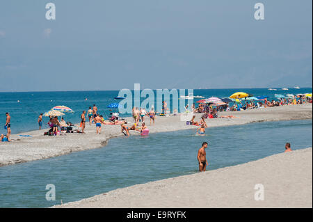 Scalea, Calabria, Italy. Holidaymakers on the beach, where the river runs into the sea - Stock Photo