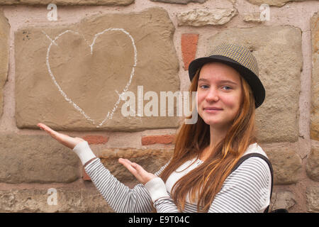 Cute young girl near a wall painted chalk heart and arrow. Falling in love concept. - Stock Photo