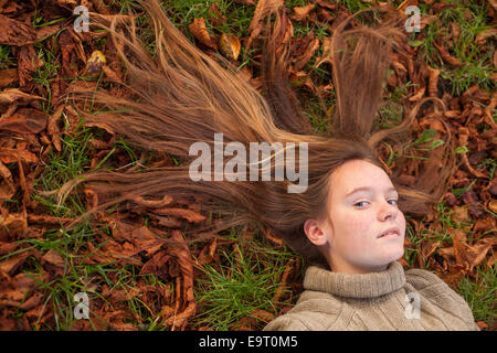 Young beautiful girl lying on autumn ground with yellow fallen leaves. - Stock Photo