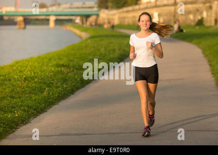 Young girl on a treadmill in the city. Healthy lifestyle. - Stock Photo