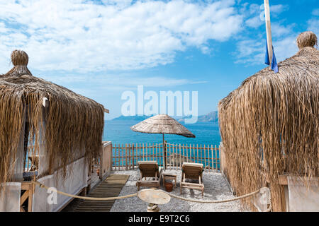 Beach huts, parasol and deck chairs in front of beautiful ocean - Stock Photo
