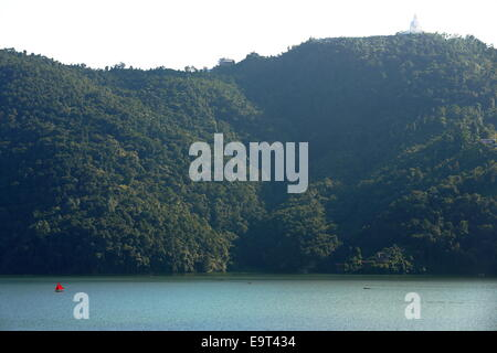 The 5.23 km2 Phewa lake with a red sail boat and the World Peace Pagoda on top of the mountain. Pokhara town-Annapurnas - Stock Photo