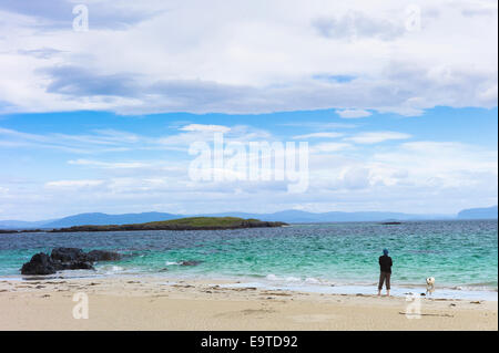 Lone person with dog on shoreline of sandy beach looking out to turquoise sea on Isle of Iona in the Inner Hebrides - Stock Photo