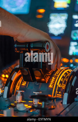 Cockpit of an Airbus A320 flight simulator that is used for training of professional airline pilots (hand on throttle - Stock Photo