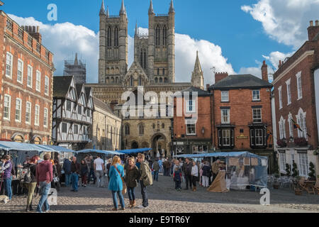 People in Lincoln market square, with cathedral in background, Lincoln, Lincolnshire, England UK - Stock Photo