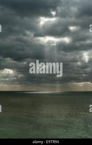 Sun rays bursting through a stormy cloudy sky over the sea in the UK - Stock Photo