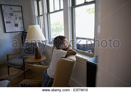 Boy with headphones looking out living room window - Stock Photo