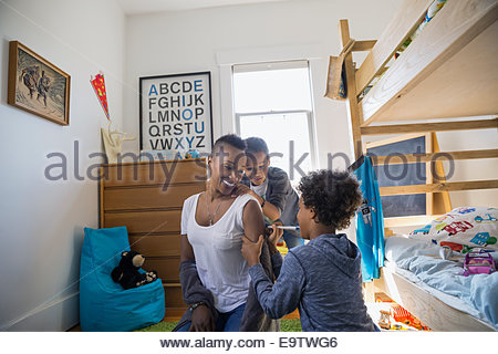 Son drawing on mother arm in bedroom - Stock Photo