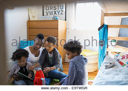 Mother and children reading story in bedroom - Stock Photo