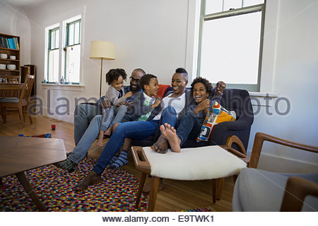 Family laughing on living room sofa - Stock Photo
