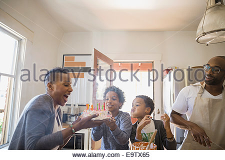 Family watching mother blow out birthday cake candles - Stock Photo