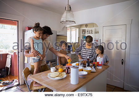 Family preparing breakfast in kitchen - Stock Photo