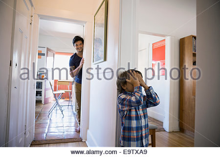 Father and son playing hide-and-seek - Stock Photo