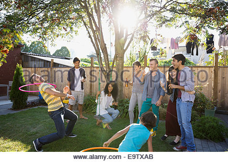 Friends playing with plastic hoop in backyard - Stock Photo