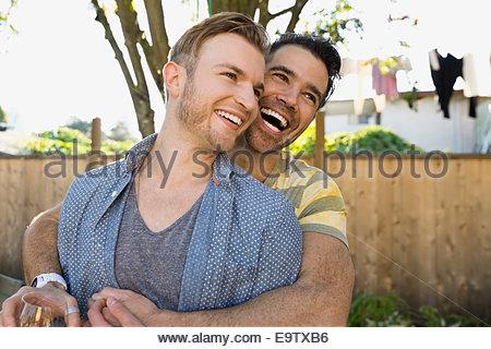 Homosexual couple hugging in backyard - Stock Photo