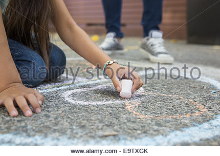 Girl drawing hopscotch number 8 with sidewalk chalk - Stock Photo