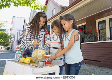 Brother and sisters at lemonade stand outside house - Stock Photo