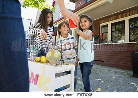 Girl serving lemonade at lemonade stand outside house - Stock Photo